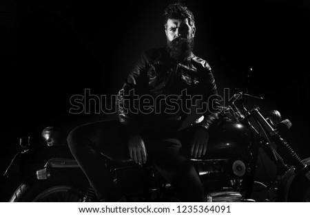 Macho, brutal biker in leather jacket stand near motorcycle at night time, copy space. Biker culture concept. Man with beard, biker in leather jacket lean on motor bike in darkness, black background. #1235364091