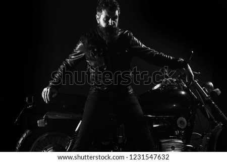 Macho, brutal biker in leather jacket stand near motorcycle at night time, copy space. Man with beard, biker in leather jacket lean on motor bike in darkness, black background. Biker culture concept. #1231547632