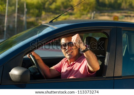 Macho driver sticking his fist out of the window