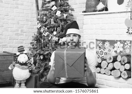 Macho hold present box with toy bear at xmas tree. Man in santa hat sit on floor at fireplace. Christmas and new year presents preparation. Boxing day concept. Happy holidays celebration.
