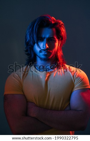 Macho man. Masculine power. Cyberpunk fashion portrait. Neon light people. Confident guy yellow t-shirt crossing hands chest dark blue red vibrant color glow isolated deep ocean. Foto d'archivio ©