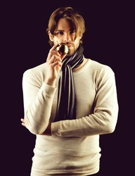 Macho man with stylish beard and haircut wearing warm scarf holds symbolic golden apple isolated on black background. Concept of assuredness and luxury goods