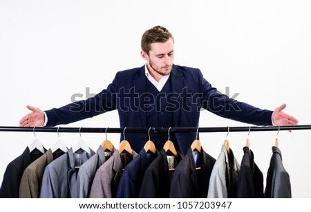 Macho on strict face presenting exclusive handmade clothes, suits on hanger. Tailors salon concept. Man in suit, client, customer, tailor, clothes designer pointing at hanger, white background. #1057203947