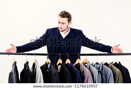 Macho on strict face presenting exclusive handmade clothes, suits on hanger. Tailors salon concept. Man in suit, client, customer, tailor, clothes designer pointing at hanger, white background. #1178610907