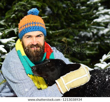 Macho with beard hugs dog, close up. Man wears knitted hatand scarf with black dog. Guy with smiling face with firtrees covered with snow on background, defocused. Friendship and allegiance concept. #1213038934