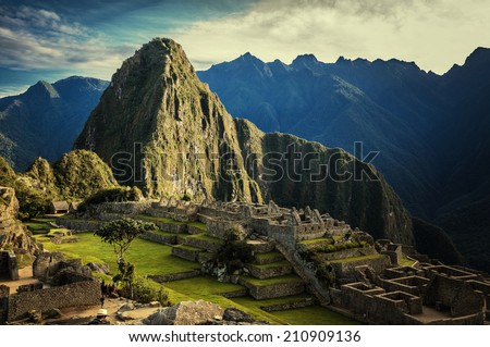 Machu Picchu at sunset when the sunlight makes everything golden-warm. Sunset at Machu Picchu, Peru. Mountain of Huayna Picchu rising above Incan ruins of Machu Picchu - Sacred Valley.