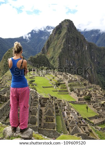 MACHU PICCHU, CUSCO, PERU - MAR 15: An unidentified woman look at a pre-Columbian 15th-century Inca site of Machu Picchu after rain on Mar 15, 2011 in Cusco region, Peru.