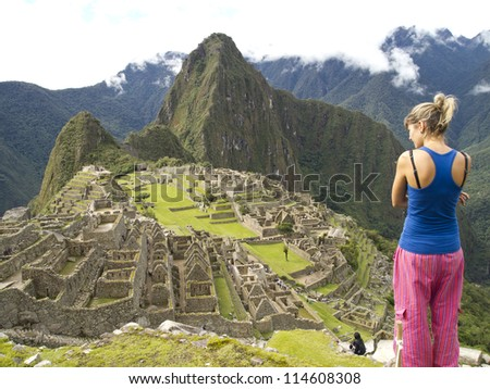MACHU PICCHU, CUSCO, PERU - MAR 15: An unidentified woman look at a pre-Columbian 15th-century Inca site of Machu Picchu after rain on Mar 15, 2011 in Cusco region, Peru. - stock photo