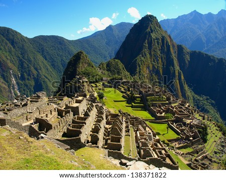 Machu Picchu in Peru - lost city of Incan Empire is UNESCO heritage. Sunny summer day with blue sky and clouds.