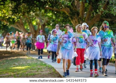 MACKAY, QUEENSLAND, AUSTRALIA - JUNE 2019: Unidentified people splashed with colored powder walking in Color Frenzy Fun Run #1431469373