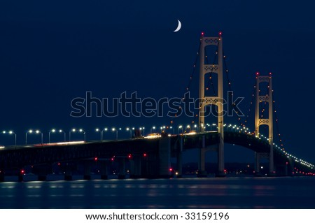 Mackinac Bridge spanning the Upper and Lower Peninsula of Michigan. Nigh shot with dark blue sky with crescent moon.