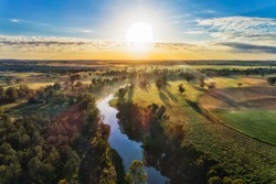 Macquarie river in Dubbo near Dundullmal homestead and farm fiels in aerial sunrise scenic view.