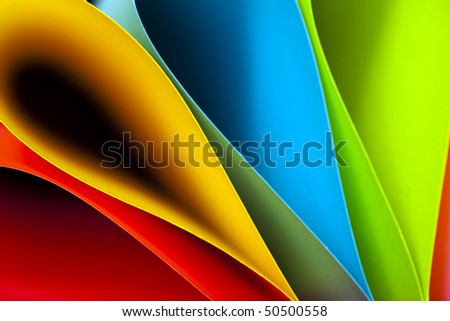 Macro and abstract image of colored card stock (blue,red,pink,yellow and green) with a tear drop or elliptical shape on a black background. Excellent image for business background.
