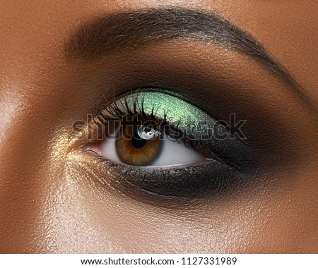 Macro and close-up creative make-up theme: beautiful female eye with green and golden shadows, black skin