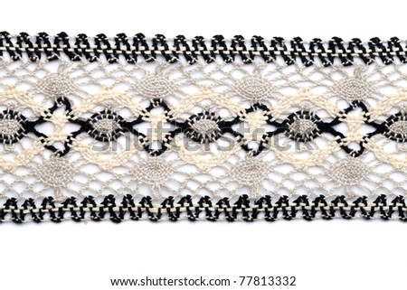 Macro black and white lace texture on brown background