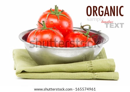 Macro close up of a bowl of fresh ripe vine tomatoes on a green napkin with sample text. Shot in studio on a white background.