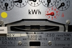 Macro close-up of a domestic kWh electric meter and slow turning measuring dial. Concept for energy, utility bills, price rise, meter reading, inflation and electricity supplier.