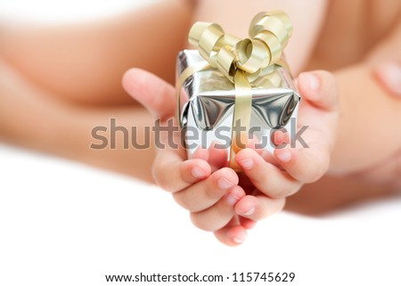 Macro close up of babies hands holding small present. Isolated.