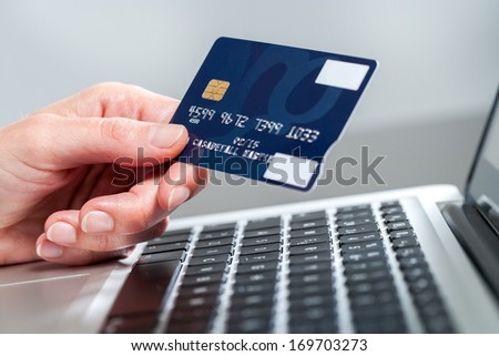 Macro close up of female hand holding credit card on laptop.