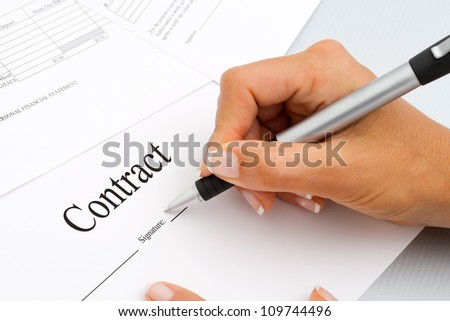 Macro Close up of female hand signing contract documents. - stock photo