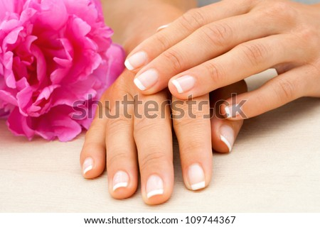 Macro close up of female hands with french manicure.