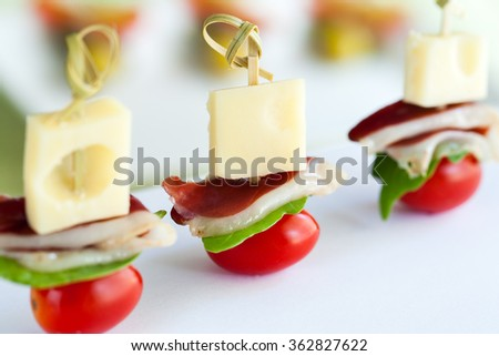 Macro close up of mini duck ham, cheese and cherry tomato appetizers mounted on skewers.