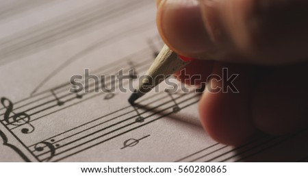 Macro close up of musician or composer hand writes a song or a musical work, writing notes with pencil on the pentagram. Concept: conservatory, music, composer, notes, art, life #560280865
