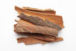 Macro close-up of Organic cinnamon ( Cinnamomum verum) or dalchini on white background. Pile of Indian Aromatic Spice. Top view