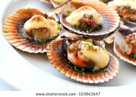Macro close up of queen scallop starter with garlic dressing.