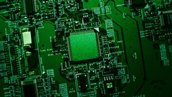 Macro Close-up Shot of Microchip, CPU Processor on Green Printed Circuit Board, Computer Motherboard with Components Inside of Electronic Device, Part of Supercomputer. Lit by Green Light.