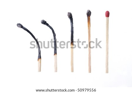 Macro closeup of a group of burned matches, one match unburned, isolated on white background