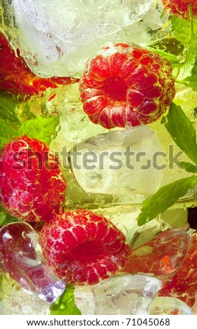 Macro closeup of a yellow cocktail drink with raspberries and mint