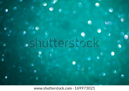 Macro closeup of abstract teal glitter texture. Shimmering blur background with shining lights. Vibrant color. #169973021