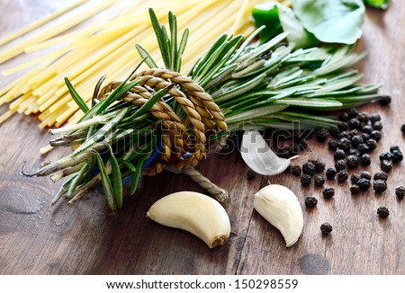 Macro composition of Italian cooking ingredients, garlic, rosemary, basil leaves, spaghetti and black peppercorns on old kitchen table shot in natural light.