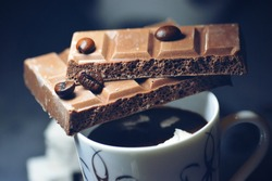 Macro cup of Coffee with chocolate bar and coffee beans