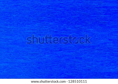 Macro detail of a blue pleated crepe paper in soft lighting