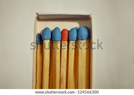 Macro detail of a box of matches (matchbox) full of matches with blue top and one different with a red top as a symbol of difference, differentness and dissimilarity