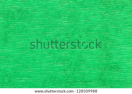 macro detail of green folded crepe paper in soft lighting