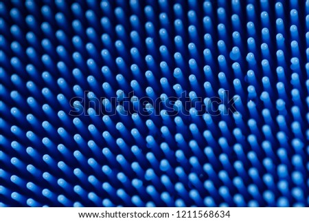 Macro detailed view of the thin bristles of a blue silicone dish scrubber, for scrubbing pots and pans.