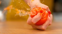 MACRO, DOF: Unrecognizable female chef with red nails squeezing a ripe organic tomato. A delicious plump tomato is squeezed by a woman with a firm grip. Organic vegetable explodes in a girl's hand.