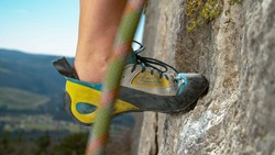 MACRO, DOF: Unrecognizable woman rock climbing up a challenging cliff steps off an edge next to chalked up crimp grip. Rock climber wearing colorful shoes steps up while ascending a steep boulder.