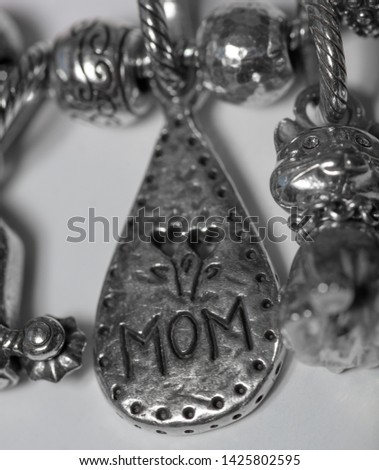 macro extreme close up of charms from a charm bracelet with mom engraved on it.