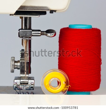Macro image of a sewing machine and reels with thread