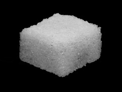 Macro image of a sugar cube isolated on a black background