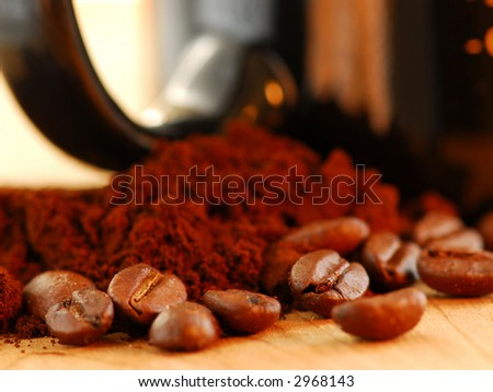 Macro image of coffee beans, ground coffee and black coffee mug