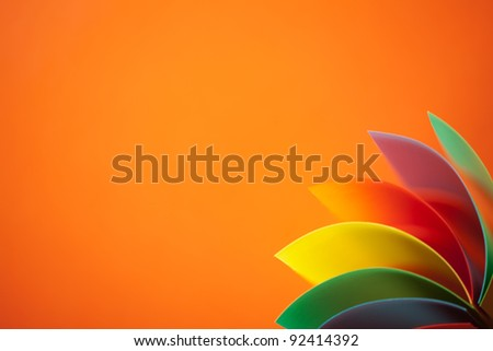 macro image of colorful curved sheets of paper shaped like a fan, on orange background
