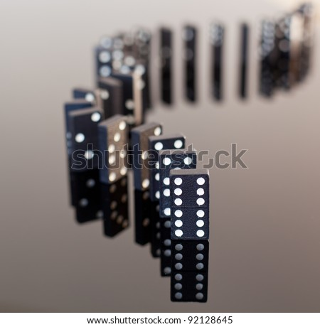 Macro image of dominos on a black reflactive surface and standing in a row