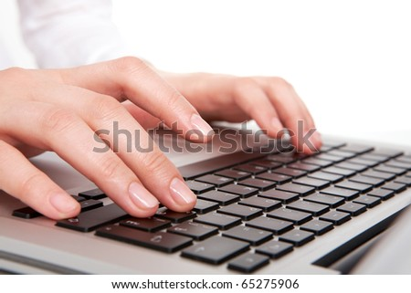 Macro image of human hands typing on keyboard