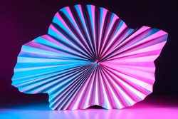 Macro image of paper folded in the form of a fan. Abstract geometric background in neon lighting. Partially blurred three-dimensional image of a paper object.