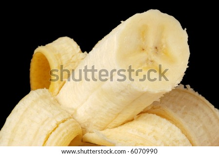 Macro image of partially peeled banana with black background